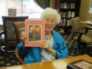 "Photo of Su holding ""Absurdities by Suzanne"" binder"